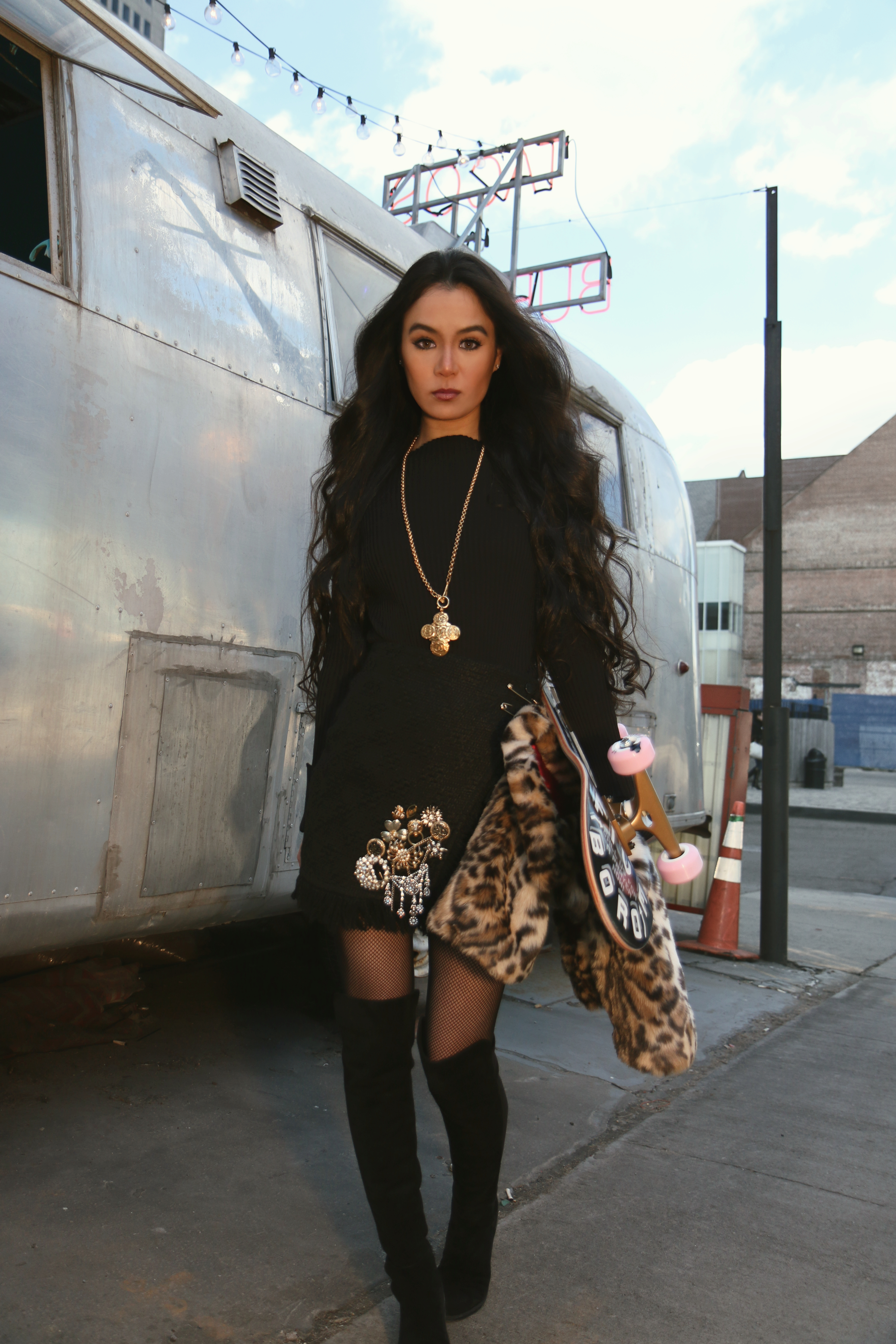 Annamaria Stewart, nyc fashion blogger at the shopping patch, wearing all black ribbed asymmetrical sweater with black boucle wrap skirt from zara, a vintage 90's gold chanel chain necklace, leopard print faux fur jacket, stuart weitzman 5050 suede boots, and the cinco barrios skateboard from 5boro, pictured by vintage airstream trailer at El Luchador