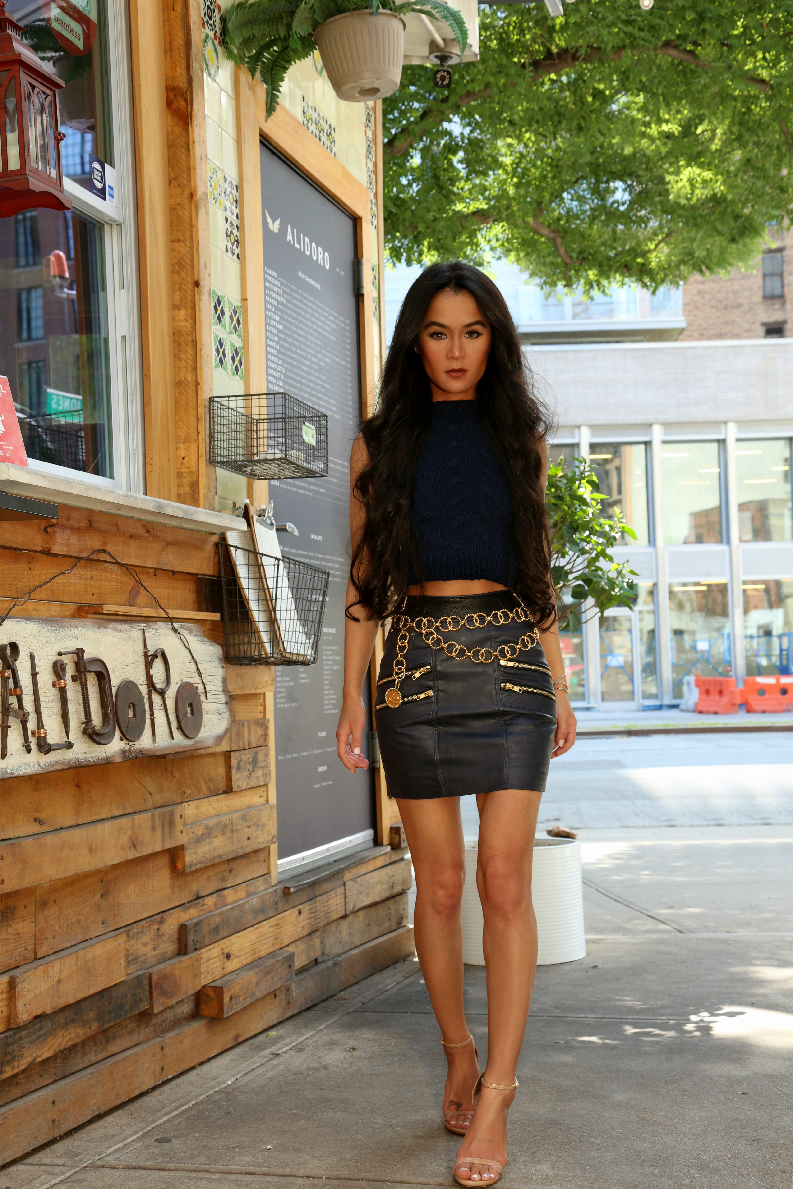 NYC Style Blogger Annamaria Stewart wearing a cropped cable sweater by Maria Dora, Self-Portrait navy leather moto skirt, vintage gold 90s Chanel chain belt, and Stuart Weitzman Nudist Sandals, pictured at The Bowery Market in NYC - The Shopping Patch