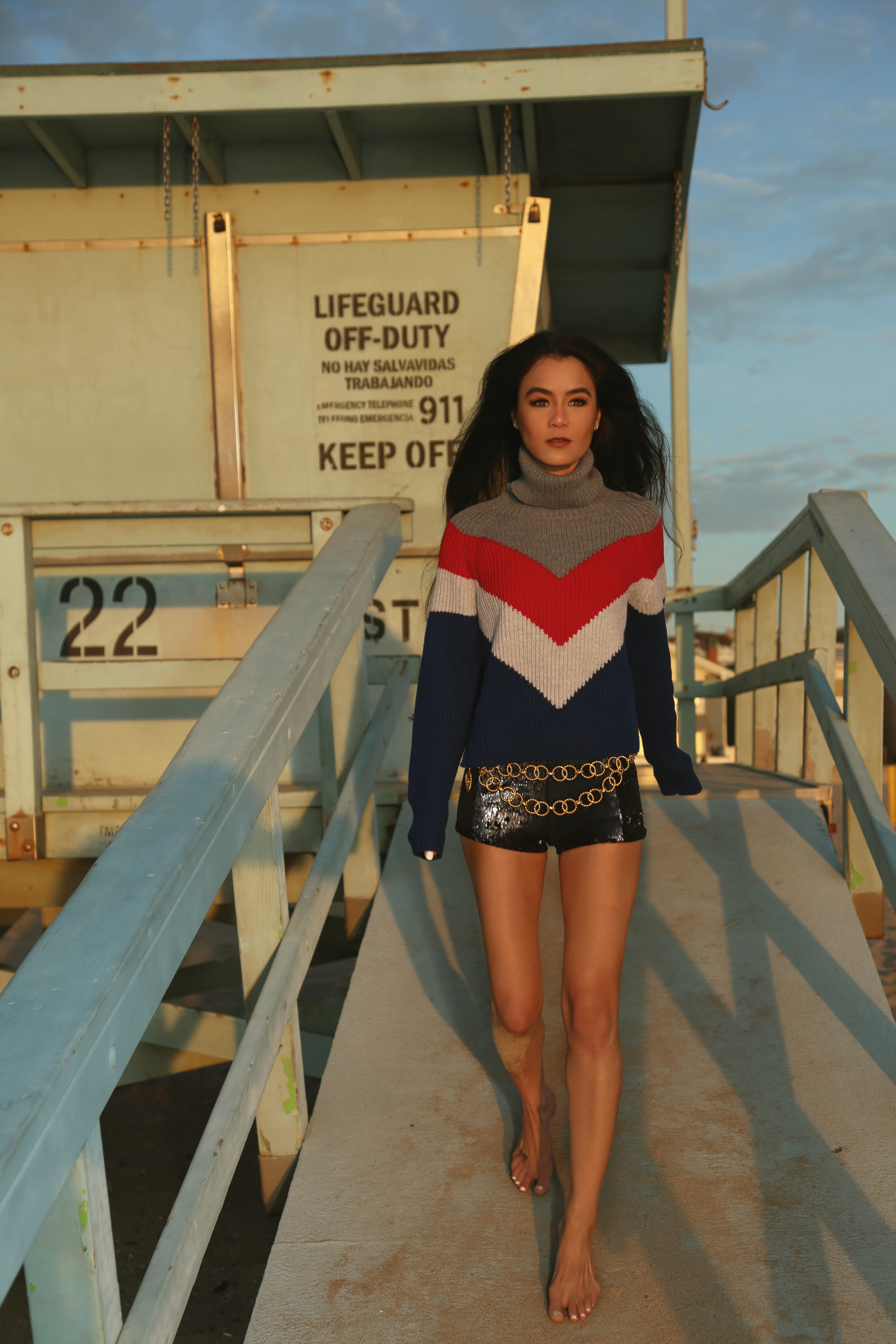 NYC Style Blogger Annamaria Stewart wearing the Wilfred Free Tilberg Cropped Turtleneck Sweater in Avalanche/Rich Red Color Block Stripe from Aritzia, High-Waisted Sequin Shorts in Navy from Silence + Noise from Urban Outfitters, and a Vintage 90s Chanel Gold Chain Belt, Pictured at a Lifeguard Stand in Hermosa Beach, California - The Shopping Patch